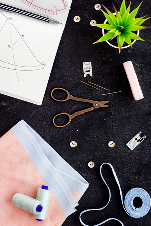 Tailor work place with thread, scissors, fabric. Sewing as hobby. Black background top view Stok Fotoğraf