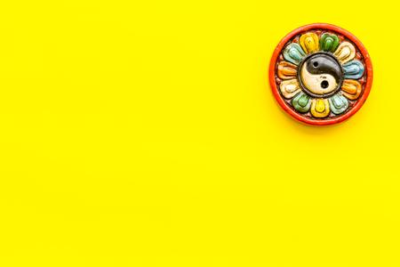 Buddhist symbol. Yin Yang symbol on yellow background top view.