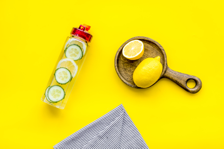 Make detox fruit water. Slices of lemon and cucumber in bottle on yellow background top view.