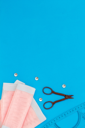 Tailor work place with thread, scissors, fabric. Sewing as female hobby. Blue background top view space for text