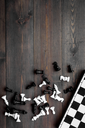 Competition or victory or strategy concept. Chess board and chess figures on dark wooden background top view copy space