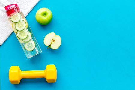 Healthy fruit water for sport, fitness. Bottle of water with lemon and cucumber near sport equipment dumbbells on blue background top view copy space
