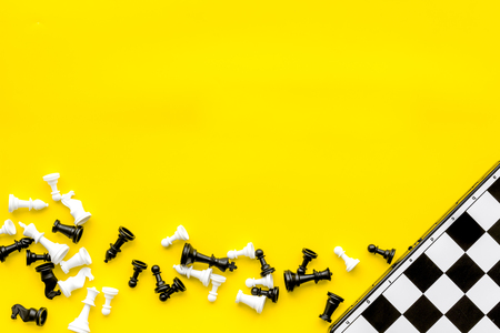 Symbol of competition. Chess board and chess figures on yellow background top view copy space