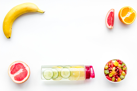 Weight loss concept. Fruit salad near fruit lemon and cucumber water on white background top view copy space frame