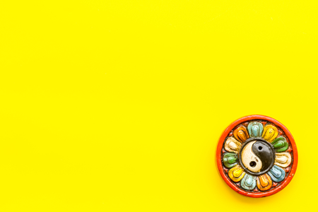 Buddhist symbol. Yin Yang symbol on yellow background top view. Фото со стока - 115475377