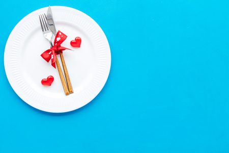 Dating on Valentines day concept. Festive dishes, tableware on plate on blue background top view space for text