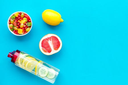 Diet rich in fruits. Slimming diet. Fruit salad near fruit lemon and cucumber water on blue background top view copy space Stock Photo