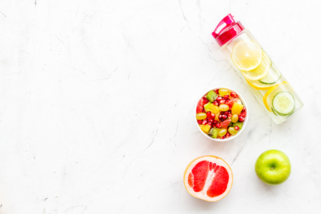 Diet rich in fruits. Slimming diet. Fruit salad near fruit lemon and cucumber water on white background top view copy space Stock Photo