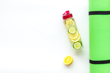 Healthy fruit water for sport, fitness. Bottle of water with lemon and cucumber near sport equipment on white background top view copy space