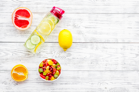 Diet rich in fruits. Slimming diet. Fruit salad near fruit lemon and cucumber water on white wooden background top view. Stock Photo