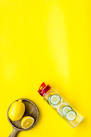 Make detox fruit water. Slices of lemon and cucumber in bottle on yellow background top view copy space