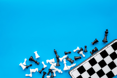 Symbol of competition. Chess board and chess figures on blue background top view. Imagens