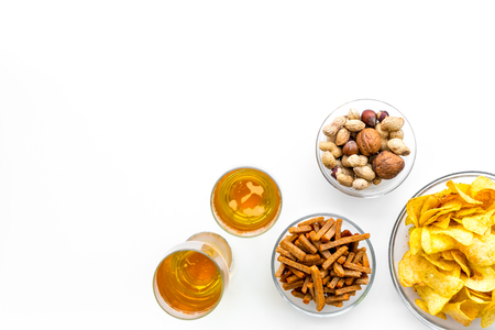 Snacks and beer. Chips, nuts, rusks near beer on white background top view copy space Stock Photo