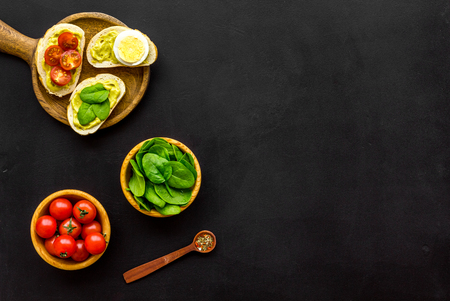 Make avocado bruschettas. Toasts with vegetables and guacamole on black background top view space for text Foto de archivo - 115569823