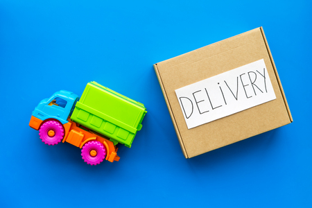 Cargo delivery concept. Cardboard box with written word delivery near toy truck on blue background top view Stok Fotoğraf