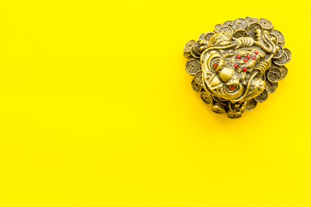Buddhist symbol. Oriental three legged toad with gold coins on yellow background top view copy space Stock Photo - 115569815