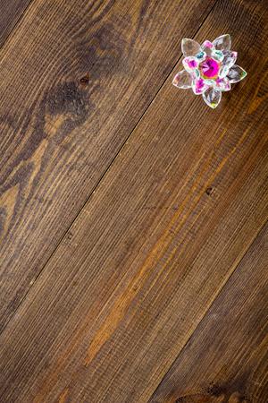 Buddhist symbol. Lotus flower on dark wooden background top view copy space