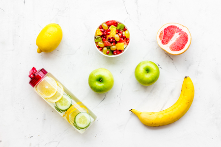 Diet rich in fruits. Slimming diet. Fruit salad near fruit lemon and cucumber water on white stone background top view Stock Photo