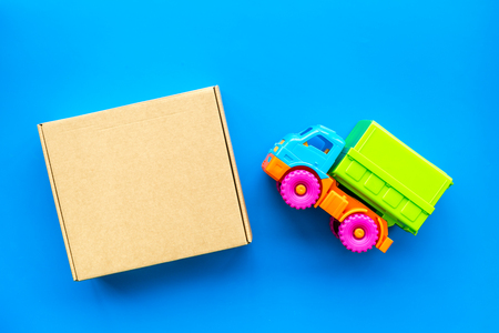 Cargo delivery concept. Cardboard box with written word delivery near toy truck on blue background top view. Reklamní fotografie