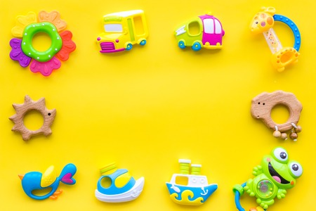 Handmade toys for newborn babies, plastic and wooden rattle on yellow background top view copy space frame