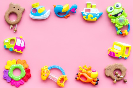 Handmade toys for newborn babies, plastic and wooden rattle on pink background top view copy space frame