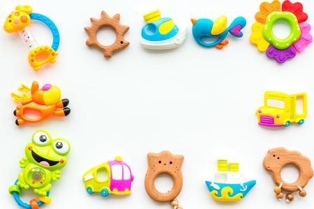Jouets faits à la main pour les nouveau-nés, hochet en plastique et en bois sur fond blanc vue de dessus copie espace cadre Banque d'images