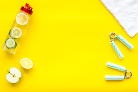 Healthy fruit water for sport, fitness. Bottle of water with lemon and cucumber near sport equipment on yellow background top view copy space