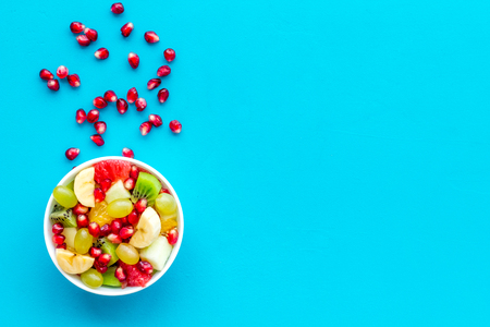 Light healthy breakfast or appetizer. Fruit salad with apple, kiwi and pomegranate in bowl on blue background top view copy space Stock Photo