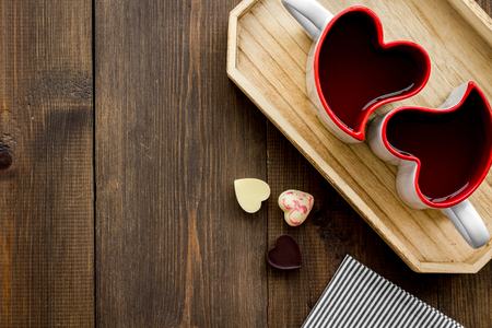Valentines day concept. Heart-shaped mugs and sweets on dark wooden background top view space for text