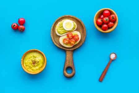 Make avocado bruschettas. Toasts with vegetables and guacamole on blue background top view
