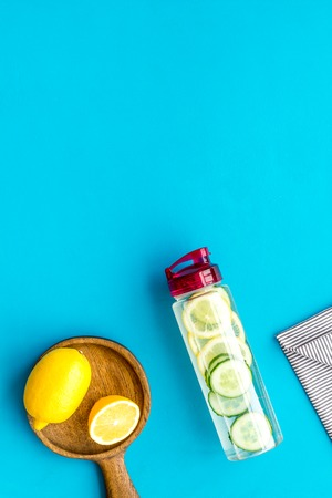 Make detox fruit water. Slices of lemon and cucumber in bottle on blue background top view space for text