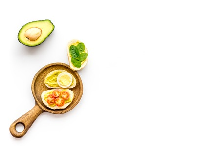 Make avocado bruschettas. Toasts with vegetables and guacamole on white background top view. Foto de archivo - 115693655