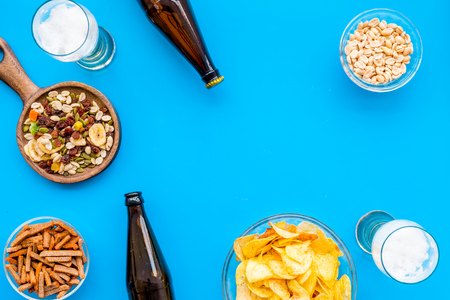 Snacks and beer. Chips, nuts, rusks near beer on blue background top view.
