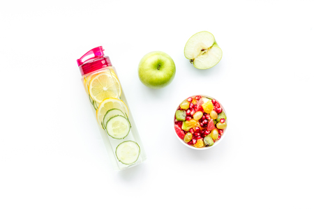 Weight loss concept. Fruit salad near fruit lemon and cucumber water on white background top view.
