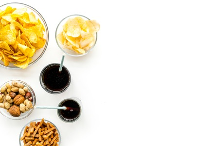 Snacks for TV watching. Chips, nuts, soda, rusks on white background top view copy space Banco de Imagens