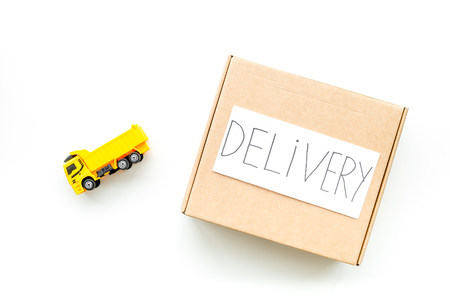 Cargo delivery concept. Cardboard box with written word delivery near toy truck on white background top view copy space