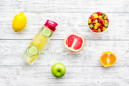 Diet rich in fruits. Slimming diet. Fruit salad near fruit lemon and cucumber water on white wooden background top view Stock Photo