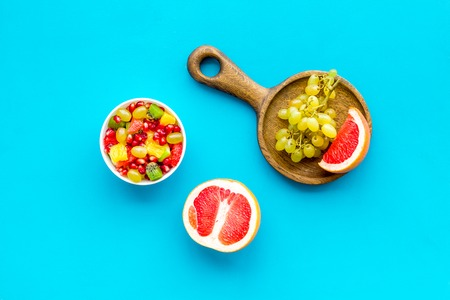 Food rich by vitamins and fiber. Healthy food. Fruit salad near fresh fruits on blue background top view Stock Photo