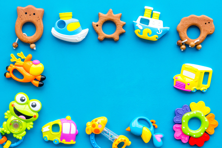Handmade toys for newborn babies, plastic and wooden rattle on blue background top view space for text frame 写真素材