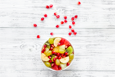 Fruit diet concept. Fruit salad with apple, kiwi and pomegranate in bowl on white wooden background top view copy space