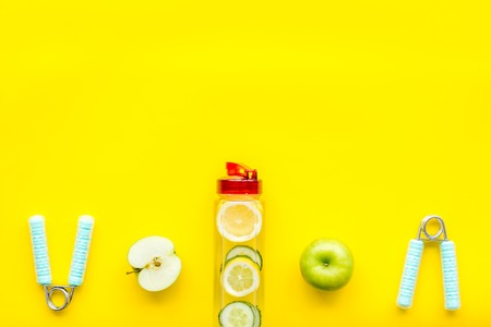 Agua de frutas saludables para el deporte, fitness. Botella de agua con limón y pepino cerca de equipamiento deportivo en el espacio de copia de vista superior de fondo amarillo Foto de archivo