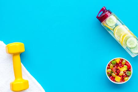 Estilo de vida saludable, hábitos saludables. Agua de desintoxicación, ensalada de frutas, mancuernas de equipamiento deportivo en el espacio de copia de vista superior de fondo azul