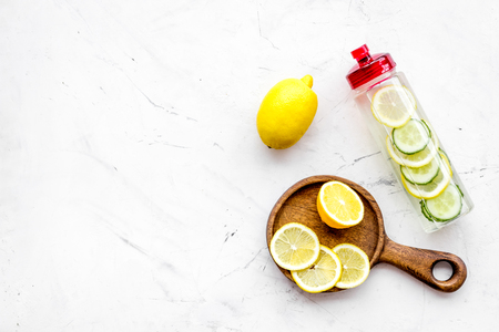Detox infused water with slices of lemon and cucumber in bottle on white stone background top view. Foto de archivo