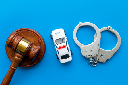 Crime concept. Police car toy, handcuff, judge hammer on blue background top view.