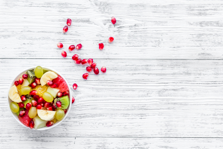 Fruit diet concept. Fruit salad with apple, kiwi and pomegranate in bowl on white wooden background top view.
