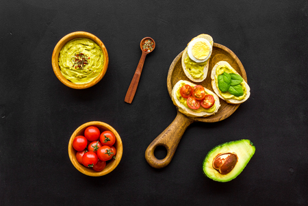 Make avocado bruschettas. Toasts with vegetables and guacamole on black background top view. Foto de archivo - 115842782