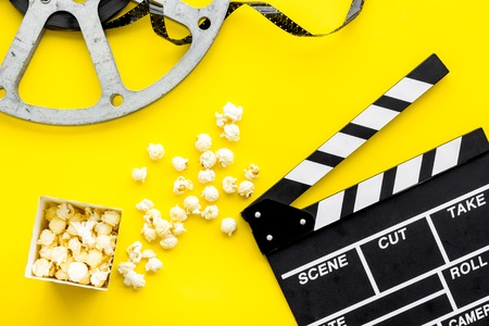 Movie premiere concept. Clapperboard, film stock, popcorn on yellow background top view. Banque d'images - 115842785