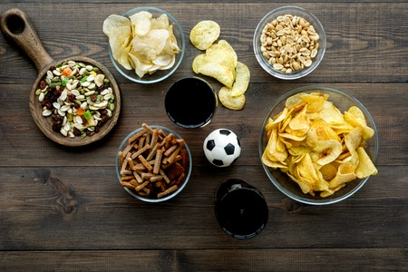 Snacks for watching football on TV. Watching sports. Chips, nuts, rusks near beer and soccer ball on dark wooden background top view.
