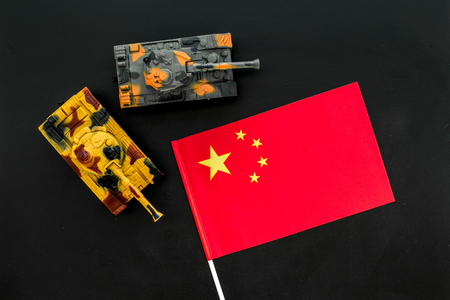 War, military threat, military power concept. China. Tanks toy near Chinese flag on black background top view.