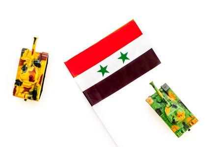 War, military threat, military power concept. Syria. Tanks toy near Syrian flag on white background top view.